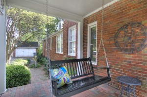 Red brick home porch with brick floor black hanging swing and black metal side table with shed and bird fountain in the background