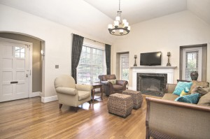 Living room with beige walls large white front door fireplace with white mantle and wood floors