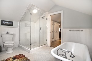 Bathroom with light blue walls white chair molding halfway up wall white tile floors white clawfoot tub white subway tile walk in shower with glass door