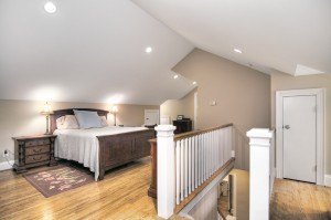 Bedroom with slanted ceiling and recessed lighting with light brown walls and wood floors white railing and wood banisters on stairs going down