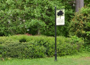 Green Country Club Heights sign on black metal post with green bushes and trees in background
