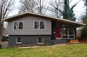Gray siding and painted brick split level home with gray and white framed windows red front door