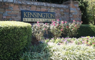 Stone wall with black and gold sign on it Kensington at Ballantyne on it with flowers and bushes planted in front