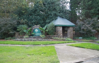 Large stone sign that says Thornhill in green and gold stone sitting area with green roof trees and green grass around it and cement sidewalk