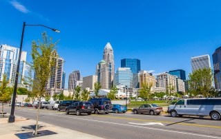 Uptown Charlotte skyline with street in front filled with cars bright blue clear sky