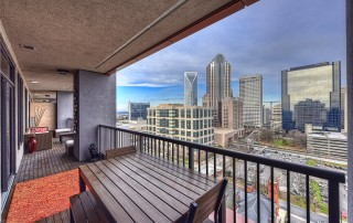 Porch with metal railing wood furniture wood floor orange rug view of uptown Charlotte skyline