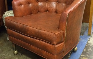 Brown leather club chair with brass studs on wheels