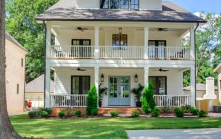 Three story white siding home black trim windows light blue double front door two story front porch black ceiling fans