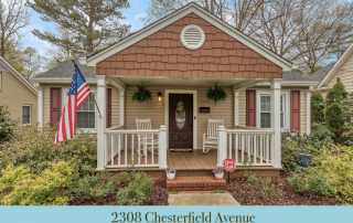 Home with tan siding brown shingles brown shutters brown front door front porch with white railing and two white rocking chairs American flag