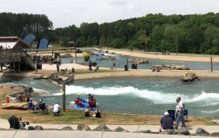 Charlotte white water center with people on rafts and trees in background