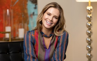 Brittany Harvey wearing a colorful blouse sitting on a black leather chair