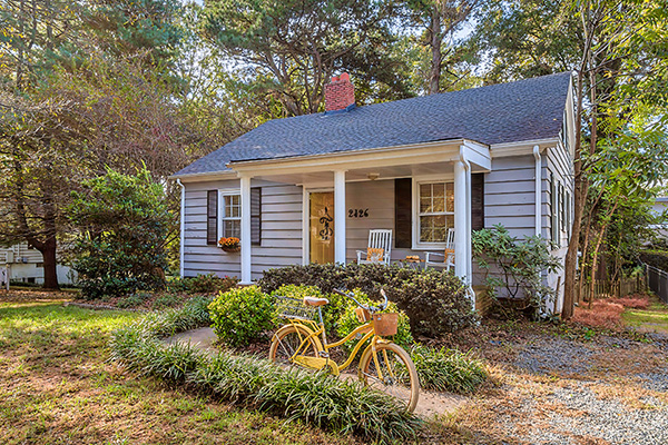 Home with gray siding black shingle roof red brick chimney black shutters front porch with white columns yellow front door yellow bike parked in front
