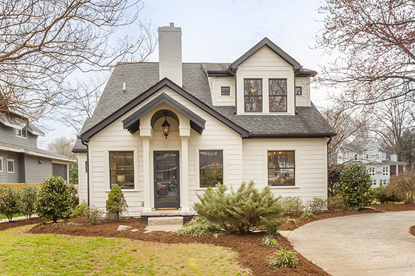 Two story home with white siding black trim windows black shingle roof white brick chimney circular driveway