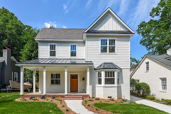 White brick and siding home black shingle roof wraparound front porch orange front door red brick front porch