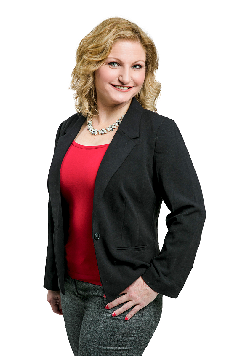 Shannon Lynch wearing a red shirt black blazer and gray pants