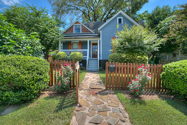Blue siding home with brown shingles brown shutters wood front door wooden fence around yard stone pathway