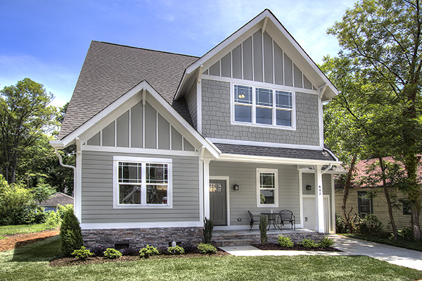 Two story home with gray siding and gray shingles white trim