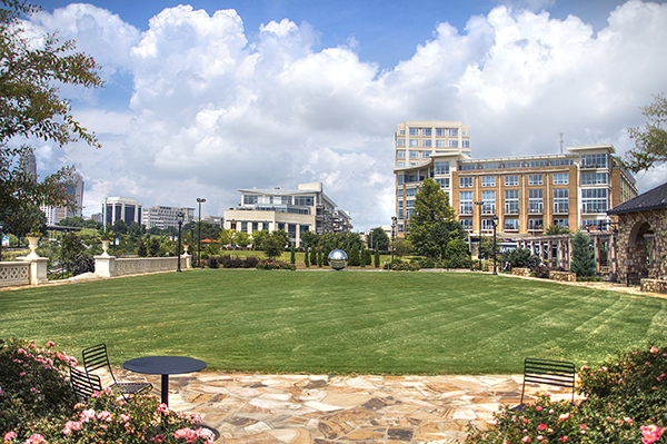 Park in uptown Charlotte with green lawn with buildings in the background