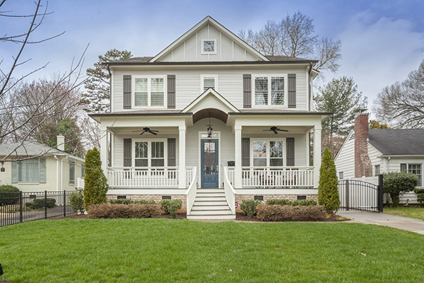 Two story home with light gray siding gray shutters large front porch with white columns and white railing two black ceiling fans on porch blue front door