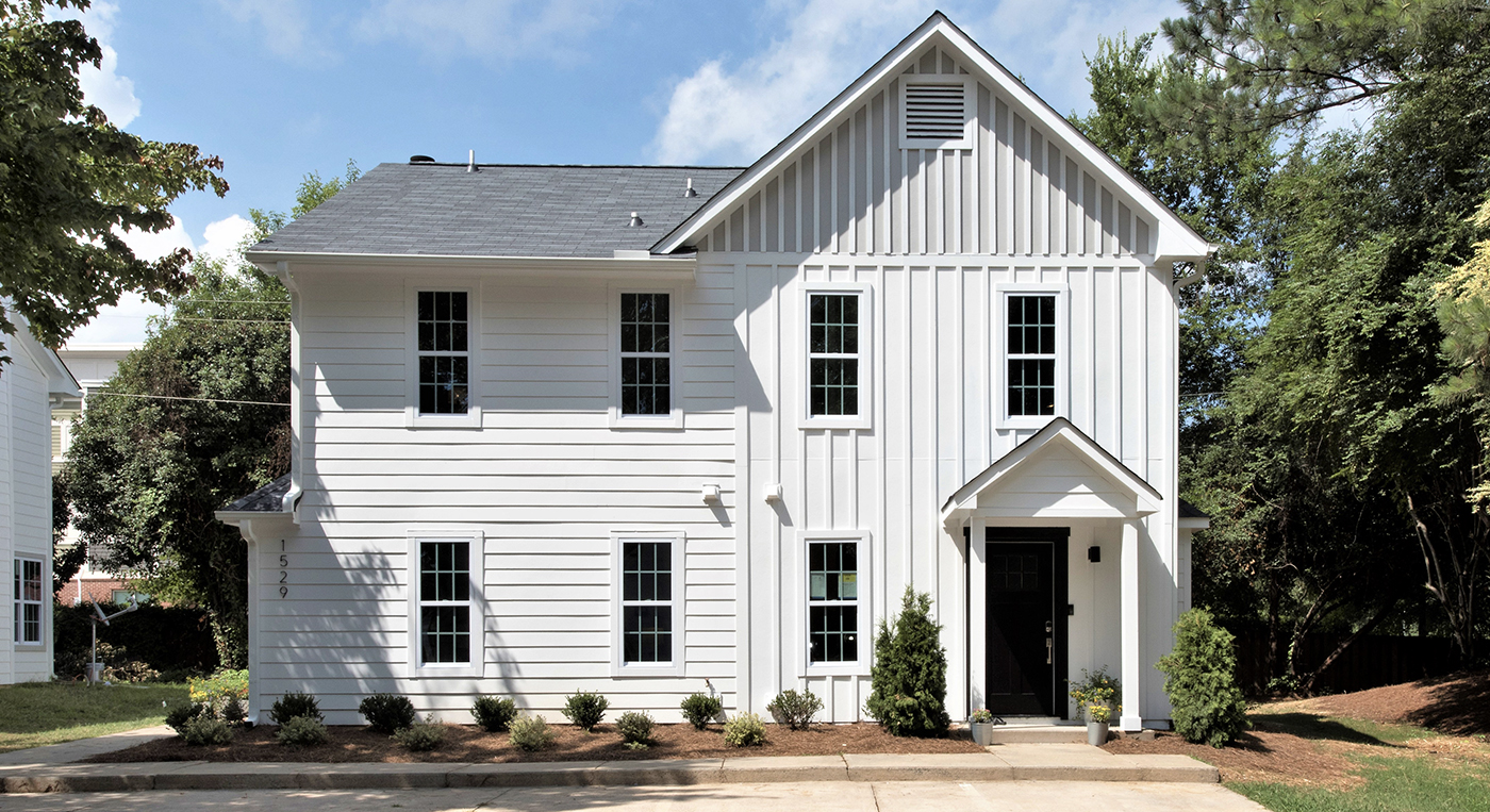 White two story condo building with horizontal and vertical siding black front door siding around building with trees around it