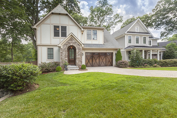 White and tan home with stone arch around front door brown barn door style two car garage brick driveway green grass front yard fenced in backyard