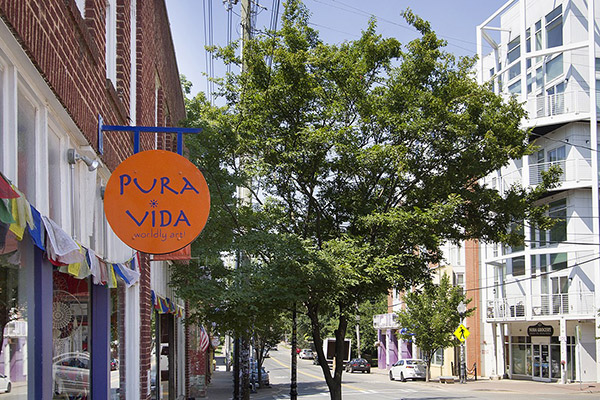 Brick building with orange and purple Pura Vida sign and tree in front