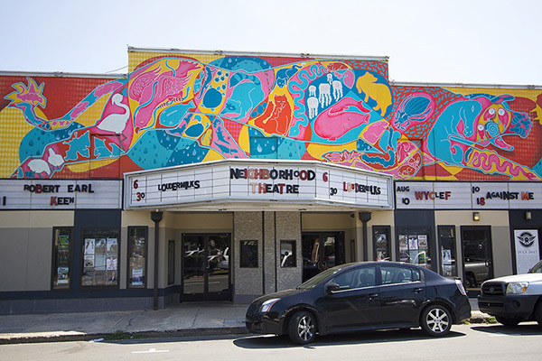Neighborhood Theatre with mural on top of building car parked in front