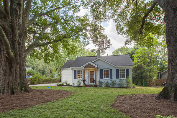 Home with gray brick blue shutters brown front door large trees in front yard