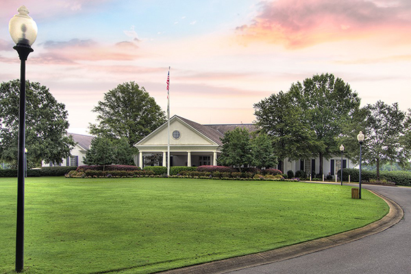 Country Club building with sunset sky large green grass circular driveway lined with lamp posts
