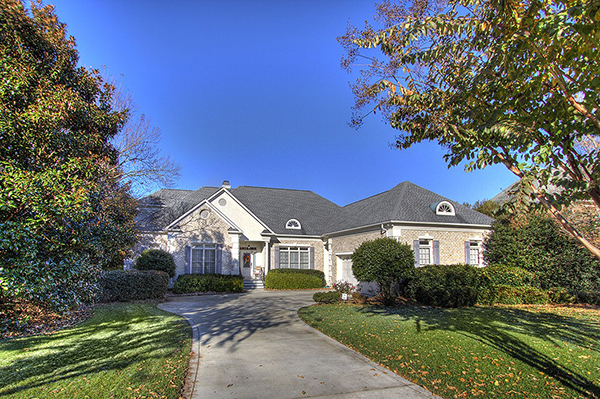 Light gray brick home with light blue shutters bushes around perimeter two car garage with circular cement driveway