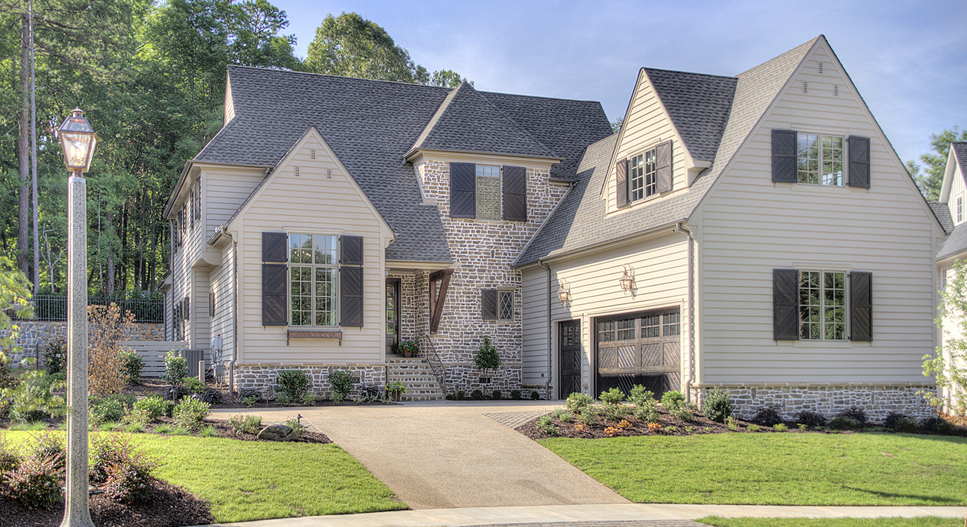 Large two story home mix of tan siding and light brick with black shutters two car garage landscaped with flowers and bushes