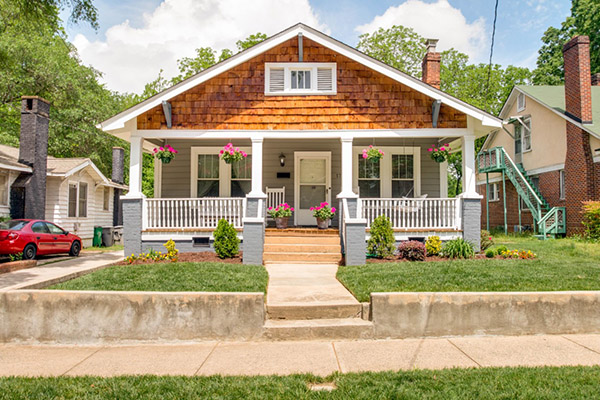 Home with gray siding and brown shingles front porch with white railing and white columns pink flowers hanging and in pots on front porch
