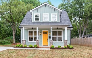 Two story home with blue siding white trim orange front door covered porch with two black ceiling fans
