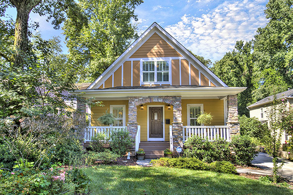 Two story orange home with brick columns white railing on front porch siding on first floor stucco on second floor