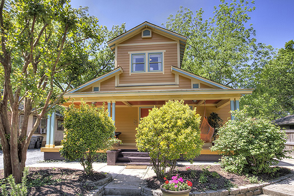 Orange siding home with front porch with teal details orange front door brown brick foundation and steps trees and flowers planted in front