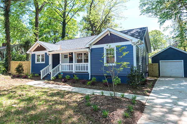 Home with blue siding white trim white railing front porch blue brick foundation and blue brick garage
