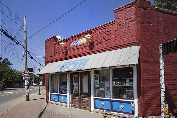 Red painted brick building with gray awning blue The Evening Muse sign brown double doors blue accents street in front