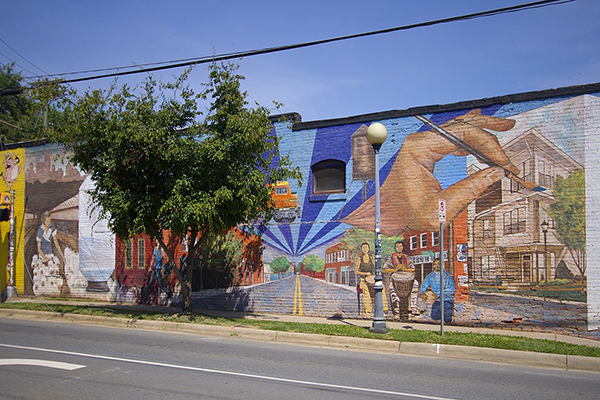 Building with. mural painted on it sidewalk with tree in front and street in front of that