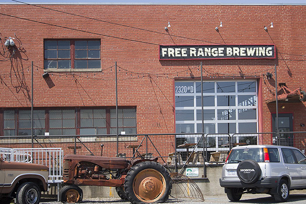 Red brick building with black white and red Free Range Brewing sign in it with two cars and a tractor parked in front
