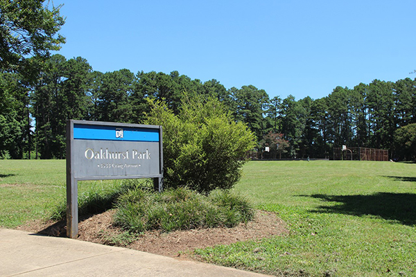 Green grass field with trees and basketball court in the background and gray and blue Oakhurst Park sign in front next to sidewalk