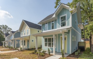 Home teal blue siding white trim yellow front door front porch with white columns cement pathway