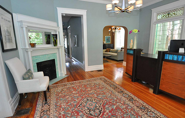 Savvy Co Real Estate Office lobby with brown wood floors blue walls white trim wood front desk blue tile fireplace
